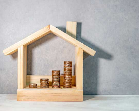 mini wooden house with coins stacked inside