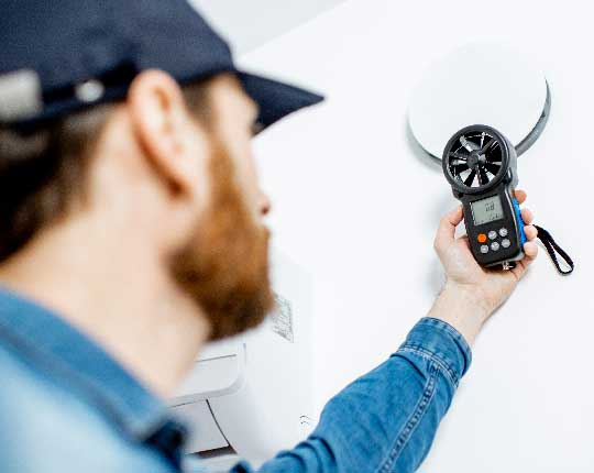 HVAC Tech measuring air quality with device in hand