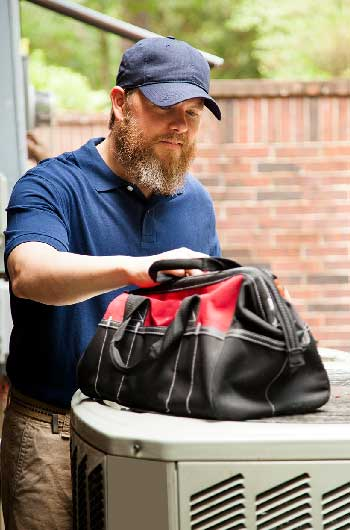 HVAC Tech wearing hat and looking into his tool bag that is on top of an HVAC unit