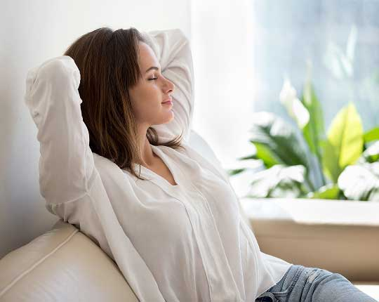 woman sitting on couch with hands behind head relaxing